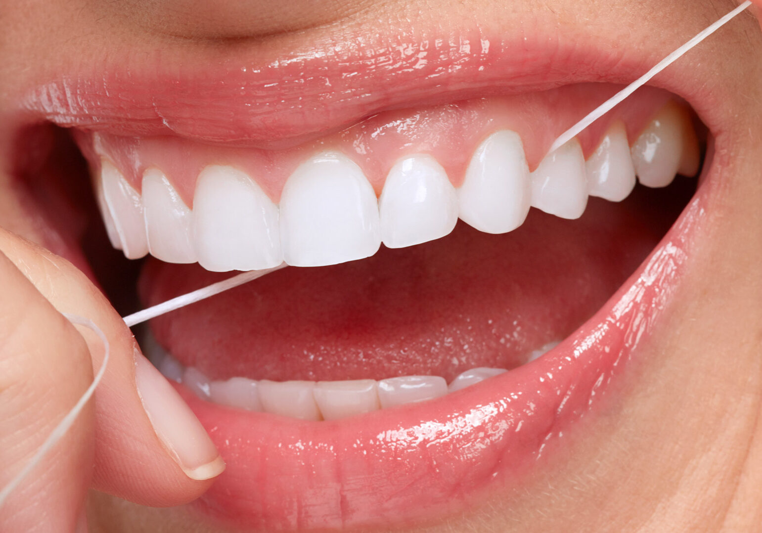 Beautiful young woman flossing white teeth. Dental health