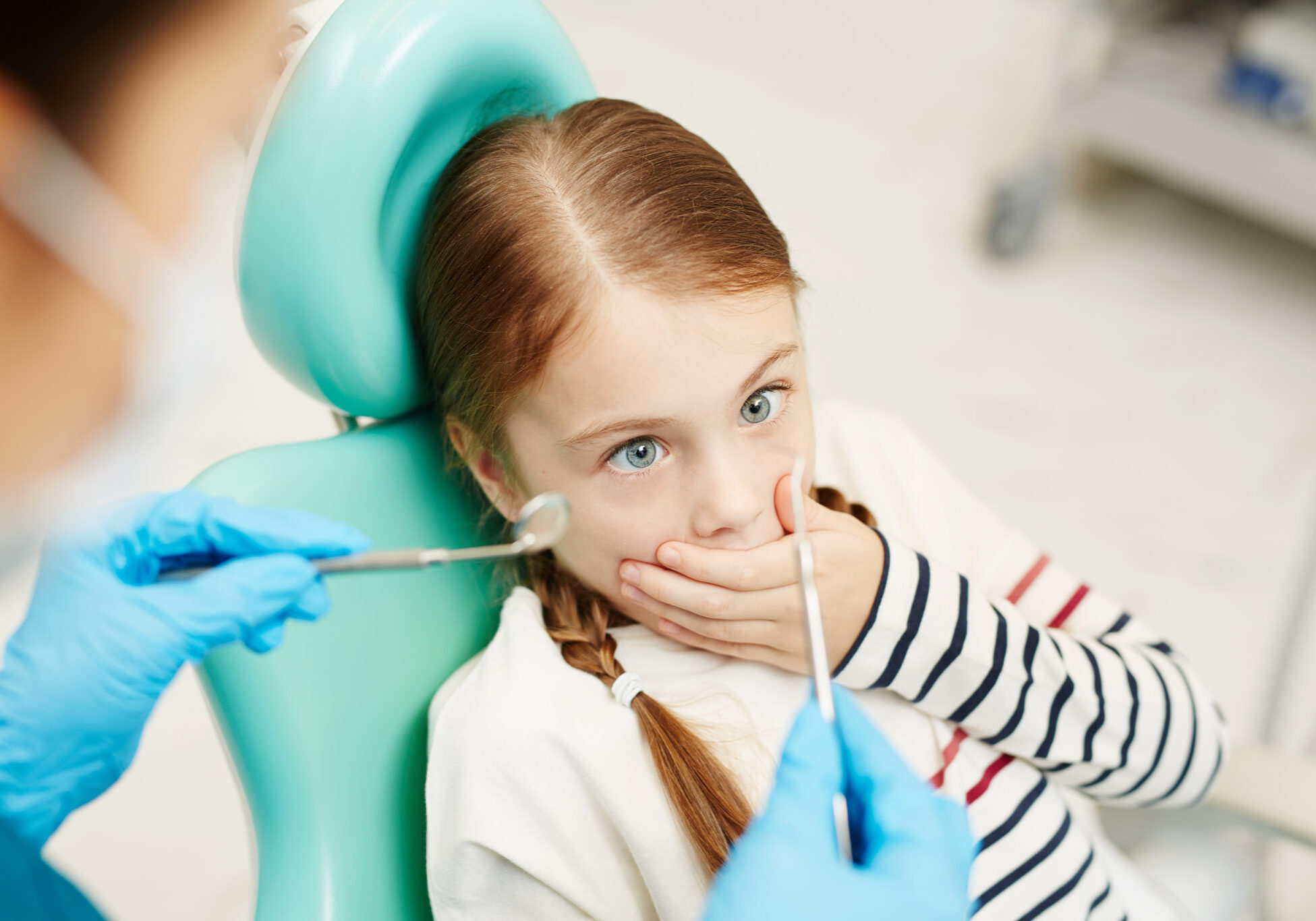 Scared little girl covering her mouth by hand while looking at dental tools for oral check-up held by dentist